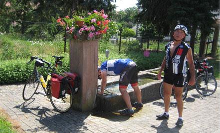 Jede Gelegenheit zur Aufnahme von Flüssigkeit konnte/musste genutzt werden. Wie hier bei der Durchfahrt eines kleinen Ortes am Rhein-Marne-Kanal. Täglich wurden je Fahrer ca. 8 Liter aufgenommen.