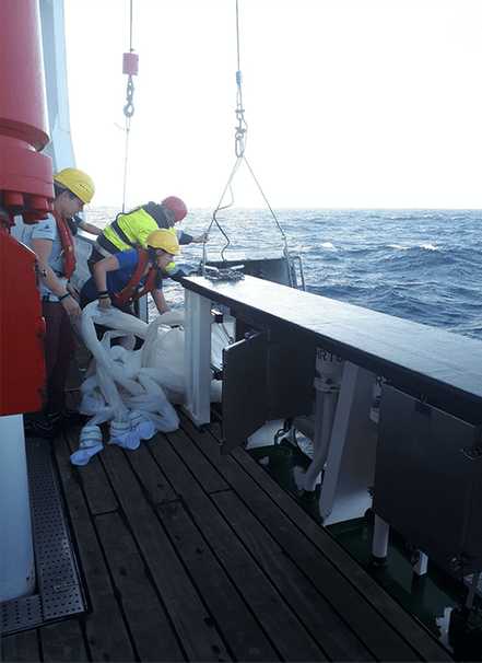 To sort the tentacles of the multinet can be a challenge! Franziska Iwan and Nicole Gatzemeier with crew member Arnold Ernst just before deployment. Image courtesy Rebecca Mensing, GEOMAR