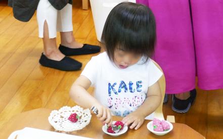 モンテッソーリの活動で1才児があけ移しのお仕事。トングを使って、イチゴのおもちゃを上手につかんでいます。