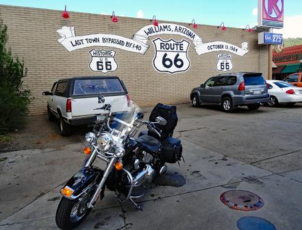 Motoglobe Motorradreisen. Die Harley steht auf einem Parkplatz und im Hintergrund an der Wand ist ein Schriftzug mit dem Namen der Route 66 sichtbar.