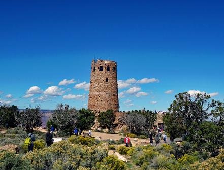 Motoglobe Motorradreisen. Der alte Wachturm am Navajo Point im Grand Canyon Nationalpark, Arizona, USA, steht vor uns umringt von Büschen und Bäumen.