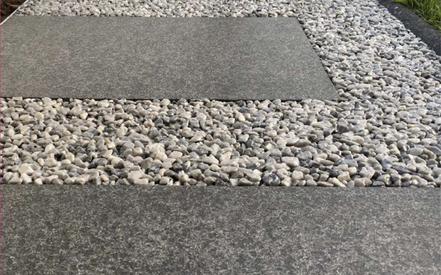 Kiesverfestigung zwischen Steinplatten im Gartenweg