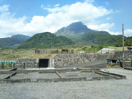 写真1 現在の雲仙普賢岳  溶岩ドーム(平成新山)と水無川を正面に見る(撮影:長井大輔)。 農業研修所跡には慰霊施設がつくられています(黒い入り口はシェルター)。