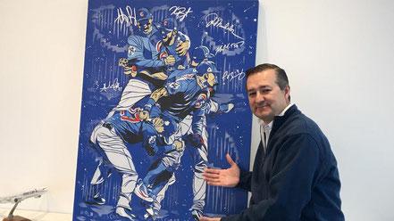 Nella foto Tom Ricketts accanto ad un disegno di Matt Szczur, artista e outfielder dei Cubs per quattro anni