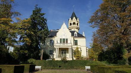 Helle Villa mit Prachtgiebel und Turm in einem Garten mit alten Bäumen, Hecken und Bänken