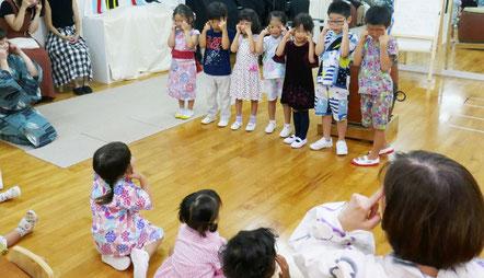 しの笛に合わせていろいろな手遊び歌を楽しみました。幼稚園児がみんなの前に出て、「上がり目・下がり目」をしてくれています。