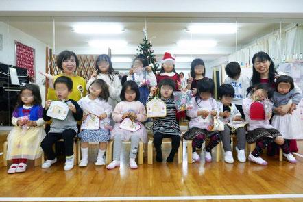 幼稚園児クラスのクリスマス会で最後に記念写真。制作したハートバッグとフォトフレームを手に笑顔がこぼれます