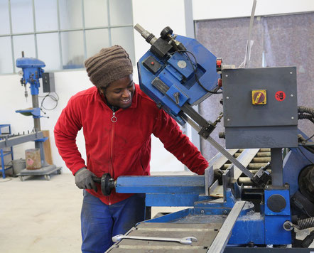 Ein Auszubildender im Metallbau arbeitet an einer Maschine.