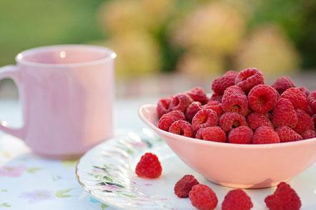 パソコンのキーボードの前に置かれたespecially for youの文字が入った桜の花びらをかたどった付箋。ピンク色のノートとボールペン。眼鏡。コーヒーの入ったピンクのマグカップ