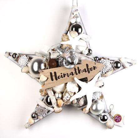 """Weißer Stern mit """"Heimathafen"""" Holzschild, Muscheln, weißem Treibholz und Glaskugeln."""