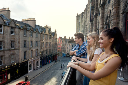 Grassmarket, a historic street in Edinburgh. Three young people on the terrace overlooking the street and terraced houses