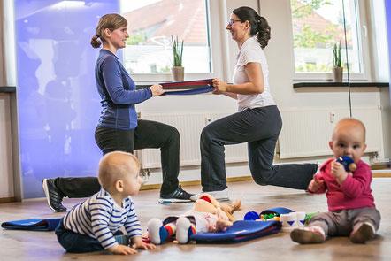Zwei Mütter machen zusammen Sport. Ihre Babys spielen.