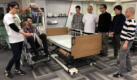 電動リフトの活用 電動リフトを活用し、特殊寝台から車いすへの移乗体験をしている場面