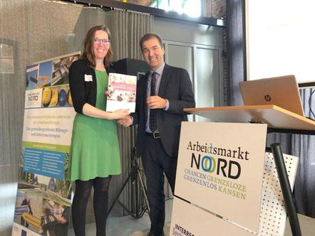 Dr. Diederich Bakker overhandigt Cora-Yfke Sikkema, burgemeester van de gemeente Oldambt, het eerste exemplaar van het onderzoeksverslag.