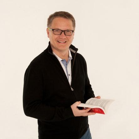Georg Möller blättert im Taschenbuch