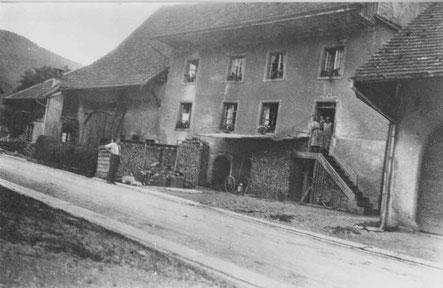 """Die """"Schmitte"""" vor dem Umbau, damals noch mit dem Hauseingang im Hochparterre, links am Haus angebaut die Wagnerei samt Scheune und Stall; rechts die Mühlescheune. (um 1936)"""