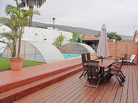 Überdachter Pool mit Rasenfläche und Holzterrasse .