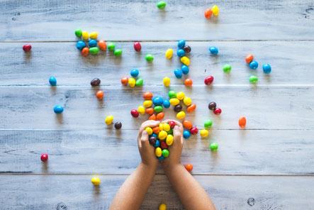 色とりどりのマーブルチョコをつかむ子供の手