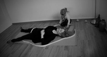 Yogamami führt Atemübung aus, währenddessen die Zweijährige mit Yoga Zubehör rundherum spielt