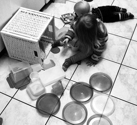 Yogikid und Yogibaby beim Kiste mit Plastikgeschirr leeren