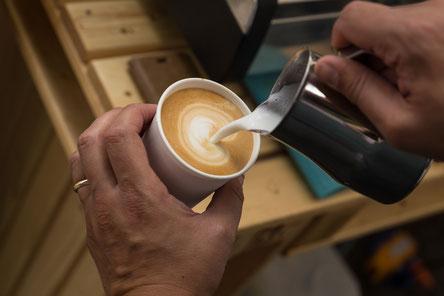 Barista macht frischen Kaffee mit Muster