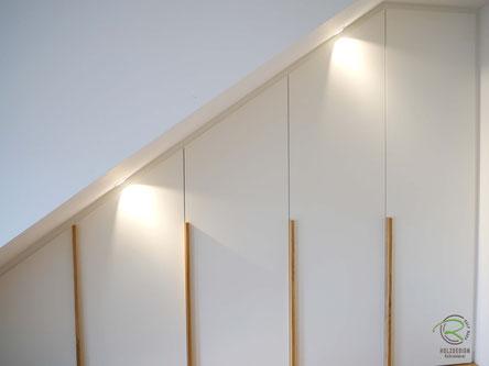 Dachnischenschrank mit Beleuchtung außerhalb dem Kleiderschrank,Drempelschrank in weiß mit Massivholz Eichen-Griffleisten, Dachschrägenschrank Schräge links mit weißen Fronten u. Massivholz-Eichengriffleisten, Kleiderschrank unter Dachschräge in weiß,