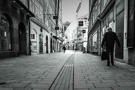 Black and white photo. An elderly man walks in the deserted Getreidegasse in Salzburg
