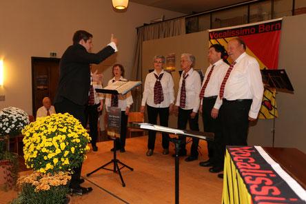 Der Chor auf der Bühne bei einem Liedvortrag, im Fordergrund der Dirigent Manfred Zimmermann