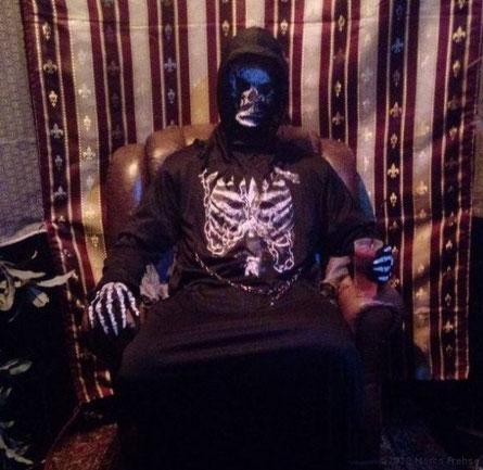 Sensenmann bzw. Tod sitzt entspannt mit einem Drink im Sessel und fungiert als Lebensberater.