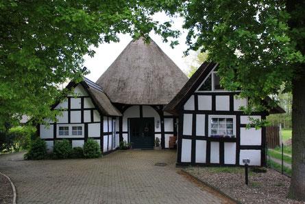 Ein Fachwerkhaus mit weißen Wänden und dunklen Holzbalken wird von den Blättern der im Vordergrund stehenden hohen Bäume eingerahmt.