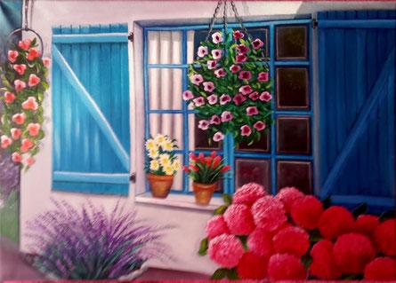 magnifique massif d'hortensias devant une fenêtre aux volets bleus.