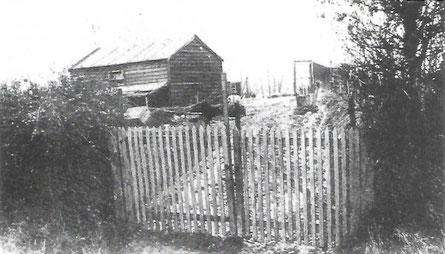 Einfahrt der Hühnerfarm mit Tor und Hütte.