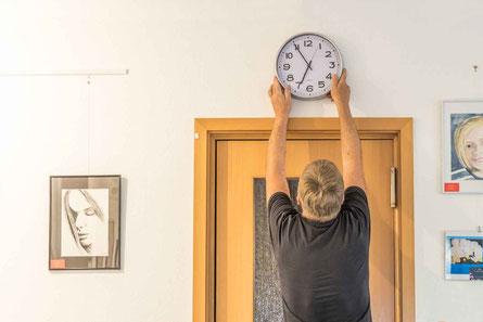 Die Uhr im Mehrzweckraum wird neu gestellt
