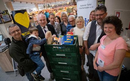 Pfarrer Bernhard Richer und Alina Schiele von der Marktleitung bei der symbolischen Warenübergabe im E-Center.