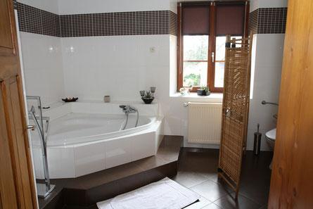 salle de bain  avec w c baignoire d'angle douche lavabo et table à langer