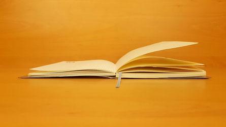 Aufgeschlagenes Buch mit gelbem Hintergrund