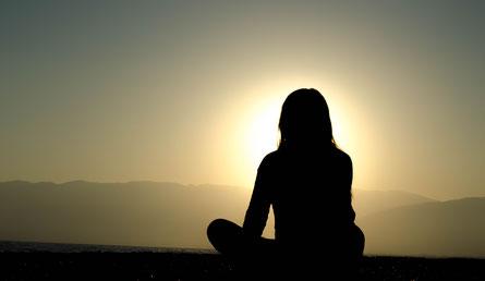 Frau meditiert in der Natur und die Sonne geht auf