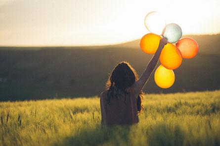 Frau mit Luftballons in der Hand in der Natur