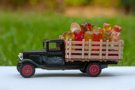 Foto zeigt ein Spielzeug Auto. Schwarzer Lieferwagen im Waltons Style. Im Teil, wo Waren geladen werden, sind viele Goldbärchen geladen.