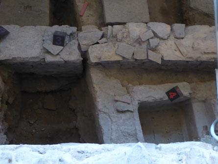 Bovenaan de vloertegels met de noordelijke galerijmuur (3) van de vroegchristelijke basiliek uit de 5e eeuw. Vooraan de rechthoekige badkuip (4) van het Romeinse thermencomplex uit de 4e eeuw.