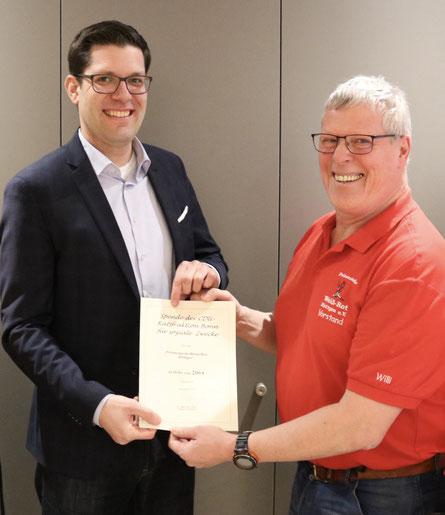 Stadtverordneter David Lutz (li.) überreicht eine Spende der CDU-Fraktion an den esrten Vorsitzenden der Prinzengarde Weiß-Rot Röttgen, Willi Juchem