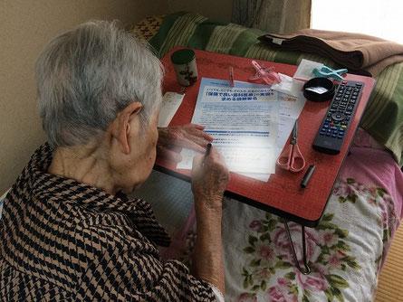 保険で良い歯科医療を求める署名に協力していただく在宅患者さん。
