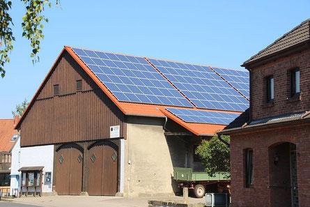 Solarpanele auf einem großen alten Haus in einem Dorf.