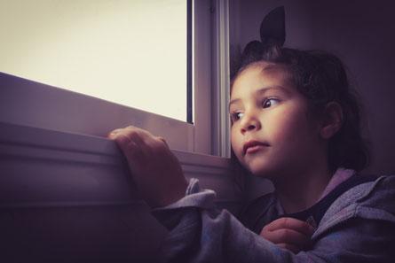 Foto: Ein Kind sitzt am Fenster und schaut nach draußen.