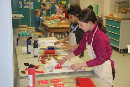 Auf den Tischen sind Walten und Farbflaschen zu sehen, Kinder stehen am Tisch und drucken mit roter und blauer Farbe. Im Hintergrund bereiten ihre Druckvorlagen vor, in dem sie sie einritzen und ausschnitzen.