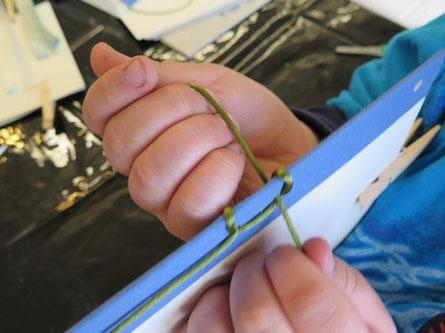 Detailaufnahme: Ein Kind zieht eine grüne Schnur durch die Löcher für die japanische Bindung.