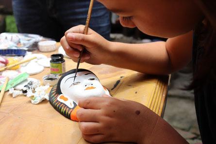 Maskenmalen in Kathmandu, Miriam malt eine Buddhamaske an