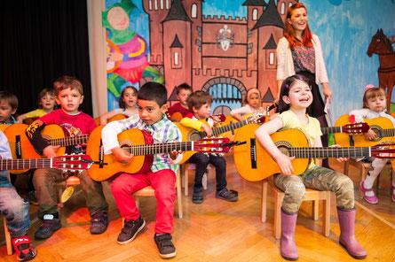 Kinder (hier bei einem Musikprojekt mehrerer Kitas in Düsseldorf) musizieren ab 4 Jahren auf der C-Gitarre