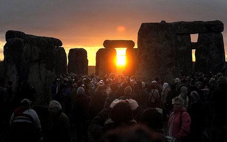 21日冬至に沈んだ太陽が再生して甦る翌日の朝日をストーンヘンジでお祝いする人々