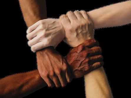 Foto zeigt zupackende Hände von vier Menschen, die sich am Handgelenk halten